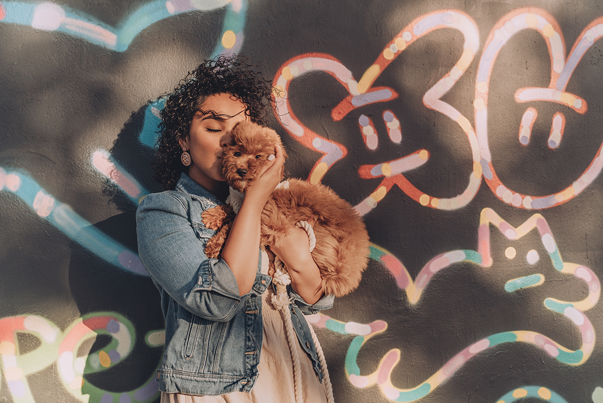 Woman holding and kissing puppy in front of decorated wall